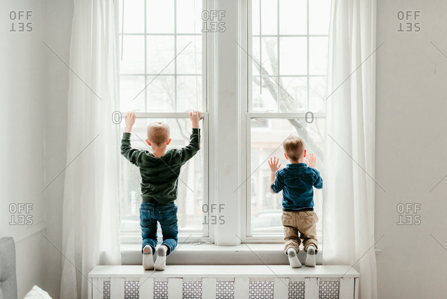 Faceless shot of two little boys looking out large windows side by side