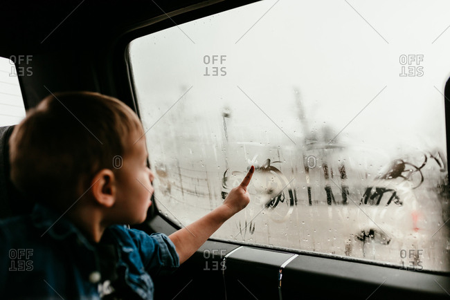 Little boy drawing on window with condensation