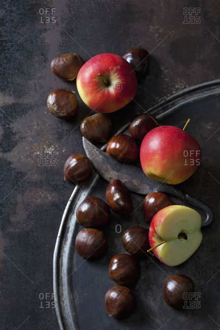 Sliced and whole apples- sweet chestnuts and an old knife on rusty background
