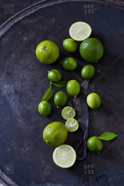Sliced and whole limequats- limes- leaves and old knife on dark ground