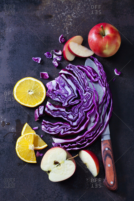 Sliced red cabbage- apples and orange slices on dark ground