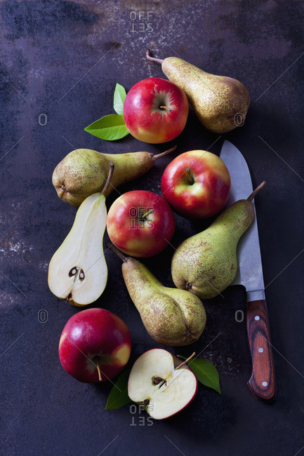 Sliced and whole apples and pears  on dark ground