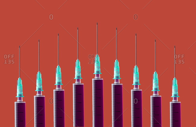 Multiple syringes organized in a pattern over orange background