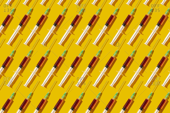 Multiple syringes organized in a pattern over yellow background