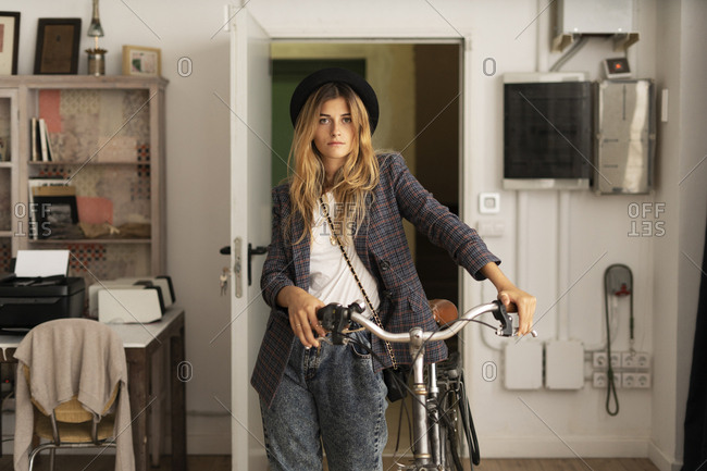 Portrait of a young woman with bicycle in a studio