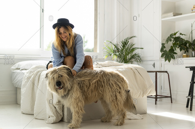 Smiling young woman sitting on bed stroking a dog