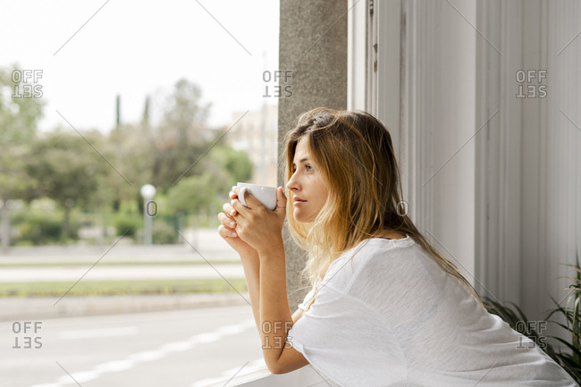 Young woman at the window holding cup of coffee