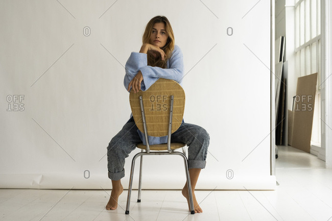 Portrait of beautiful young woman sitting on chair in studio