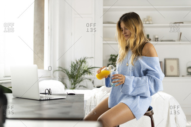 Young woman sitting in bedroom at home pouring orange juice into a glass