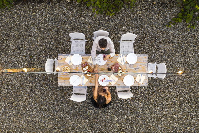 Italy- Tuscany- Siena- top view of young couple dining al fresco holding hands