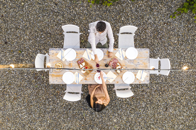 Italy- Tuscany- Siena- top view of young couple dining al fresco clinking red wine glasses