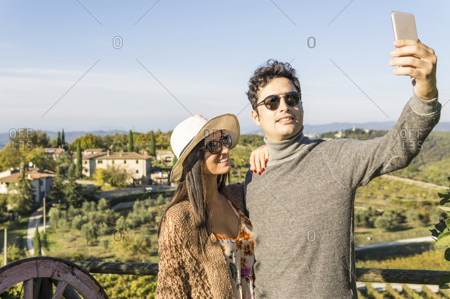 Italy- Tuscany- Siena- young couple taking a selfie at a winery