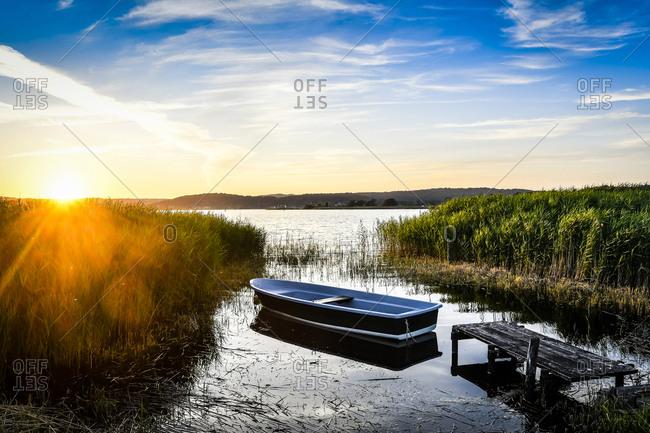 Germany- Mecklenburg-Western Pomerania- Ruegen- Sellin- empty rowing boat near jetty at sunset