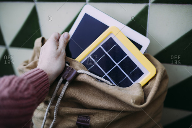 Woman putting a tablet into a backpack with a solar panel charger