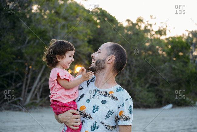 Australia- Queensland- Mackay- Cape Hillsborough National Park- happy father holding his daughter at the beach at sunset