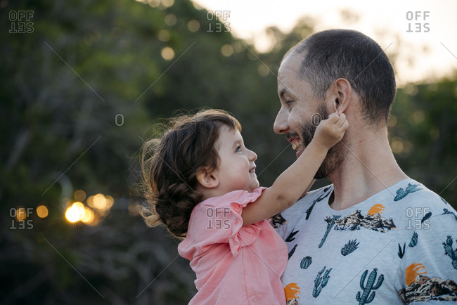Happy father holding his daughter outdoors at sunset