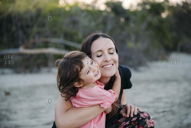 Australia- Queensland- Mackay- Cape Hillsborough National Park- happy mother hugging her daughter at the beach
