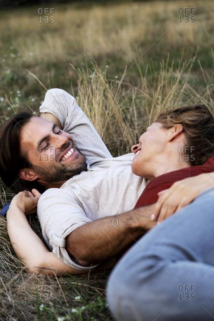 Happy couple cuddling- lying on a meadow