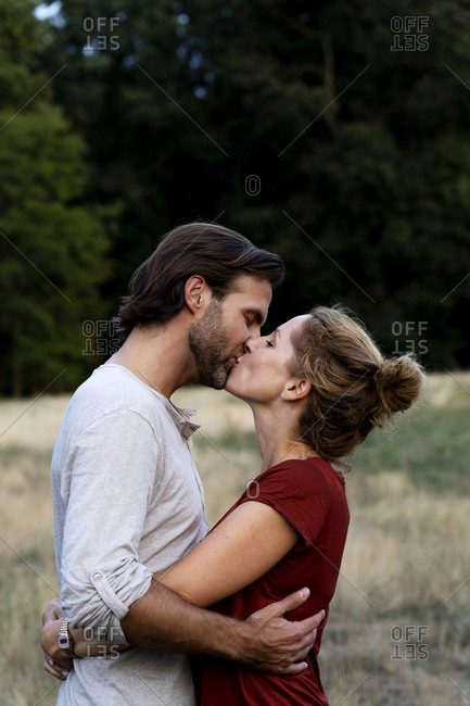 Affectionate couple kissing in nature