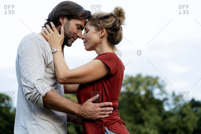 Happy couple in nature- standing face to face- caressing each other