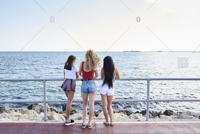 Spain- Mallorca- Palma- rear view of three young women standing at the sea