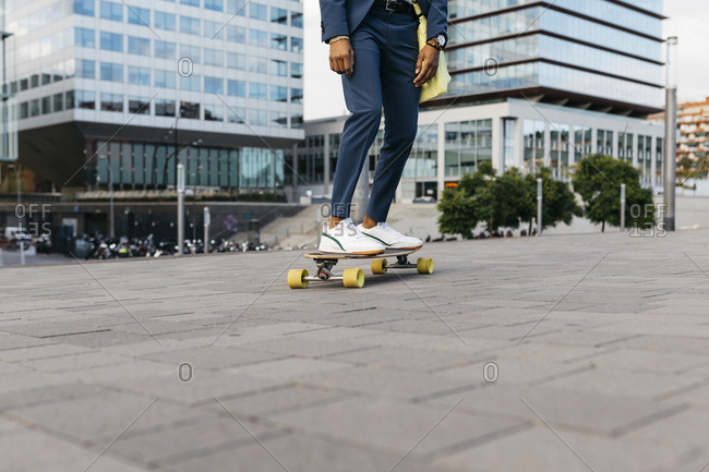 Spain- Barcelona- legs of young businessman riding skateboard in the city
