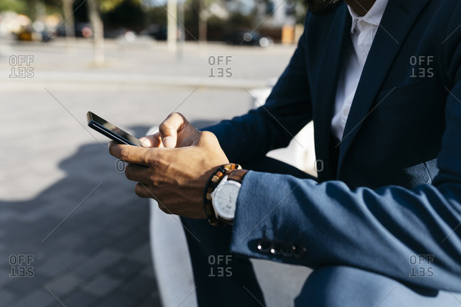 Close-upof businessman sitting outdoors using cell phone