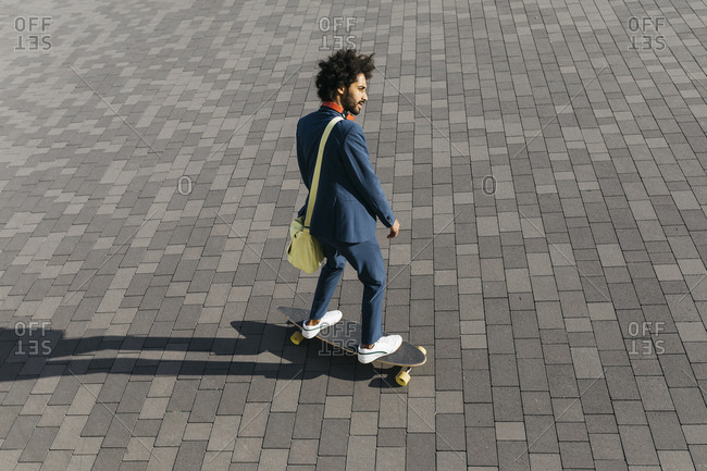 Young businessman riding skateboard on a square