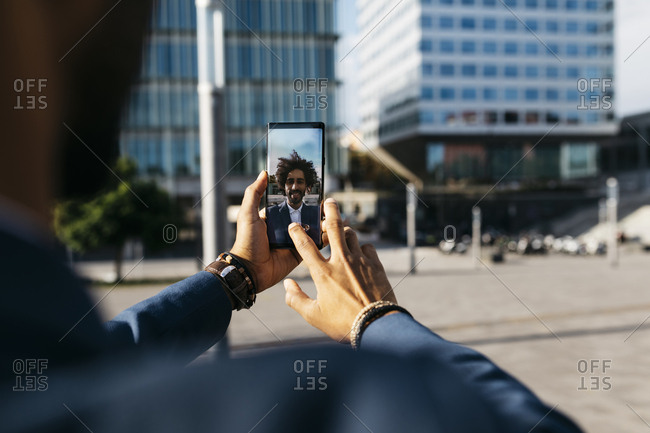 Spain- Barcelona- close-up of young businessman taking a selfie in the city