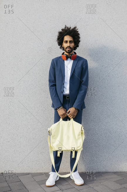 Portrait of stylish young businessman with bag and headphones at a wall