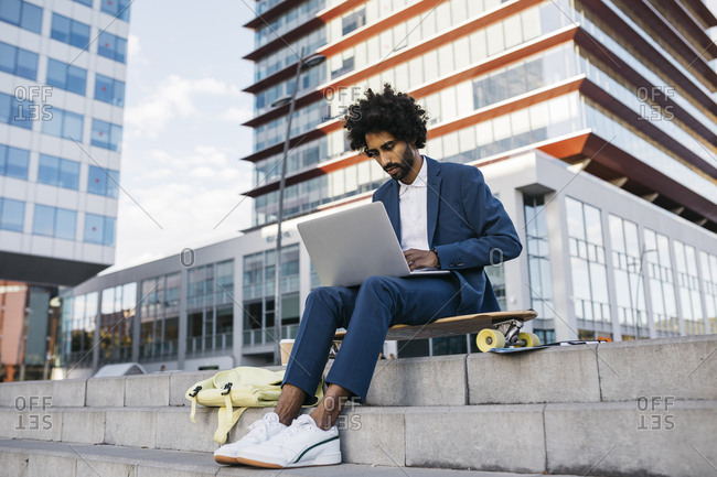 Spain- Barcelona- young businessman sitting outdoors in the city working on laptop