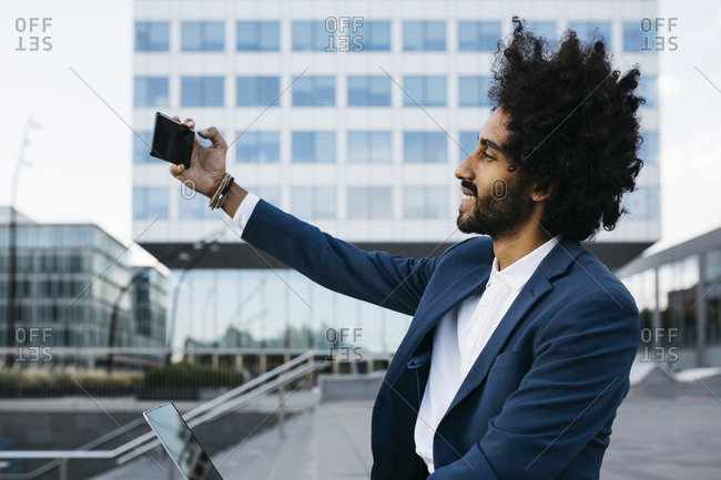 Spain- Barcelona- smiling young businessman taking a selfie in the city