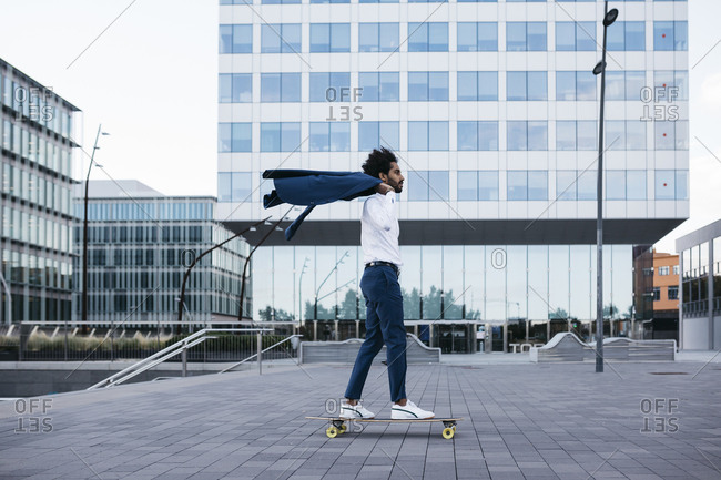 Spain- Barcelona- young businessman riding skateboard in the city