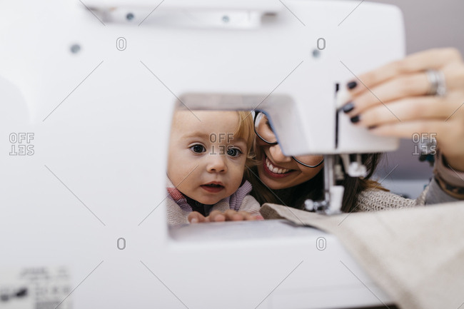 Little daughter watching her mother using sewing machine at home