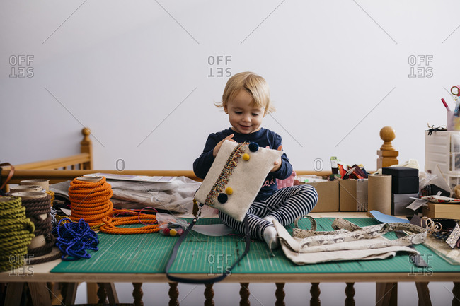 Happy little girl sitting on table with fashion accessories