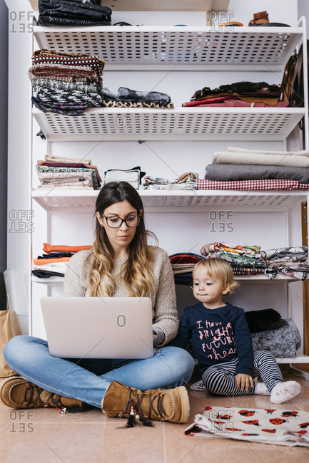 Llittle daughter watching mother sitting on the floor at home using laptop