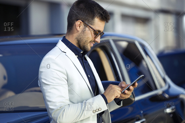successful businessman in the city- leaninagainst car- using smartphone