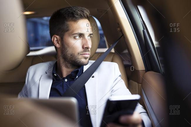 Young businessman sitting in car- using smartphone
