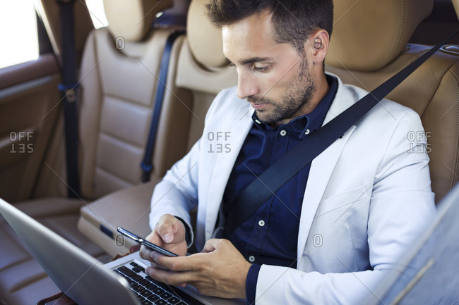 Young businessman working from the backseat of a car