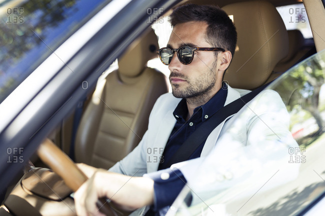 Successful young businessman driving in his car
