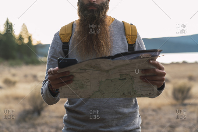 USA- North California- close-up of bearded man using cell phone and map on a hiking trip near Lassen Volcanic National Park