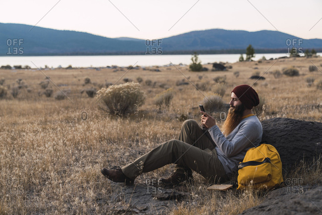 USA- North California- bearded young man using cell phone during a break on a hiking trip near Lassen Volcanic National Park