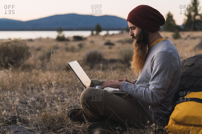 USA- North California- bearded young man using laptop near Lassen Volcanic National Park