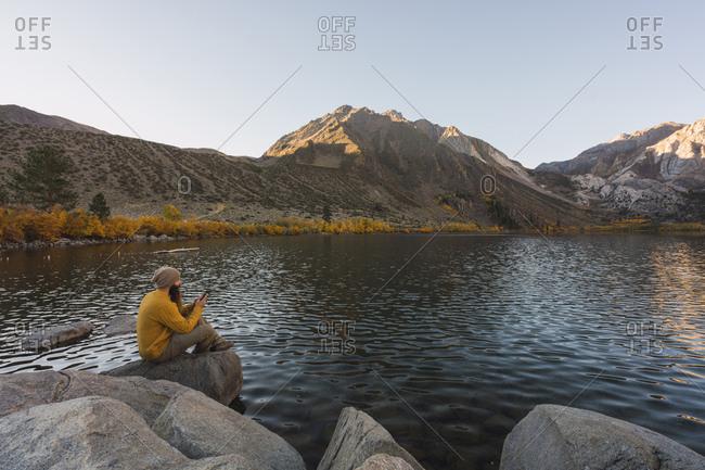 USA- California- Yosemite National Park- Mammoth lakes- hiker using smartphone at Convict Lake