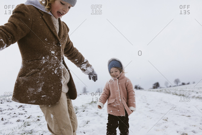 Brother and little sister playing together on snow-covered meadow