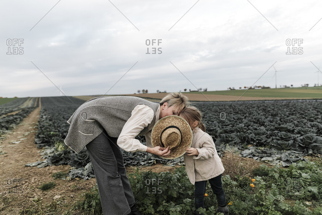 Girl and her mother with straw hat at a cabbage field