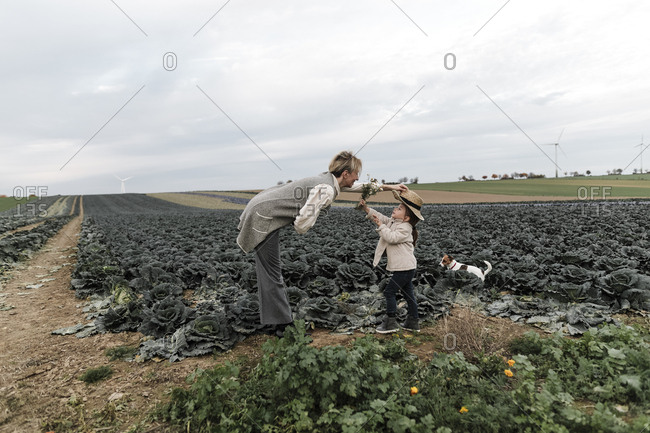 Girl and her mother with dog- straw hat and flowers at a cabbage field