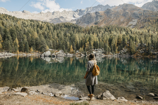 Switzerland- Engadin- woman on a hiking trip standing at lakeside in mountainscape