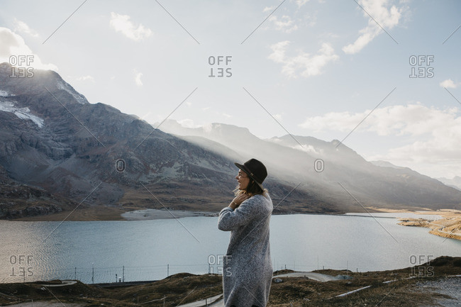 Switzerland- Engadin- woman standing at lakeside in mountainscape