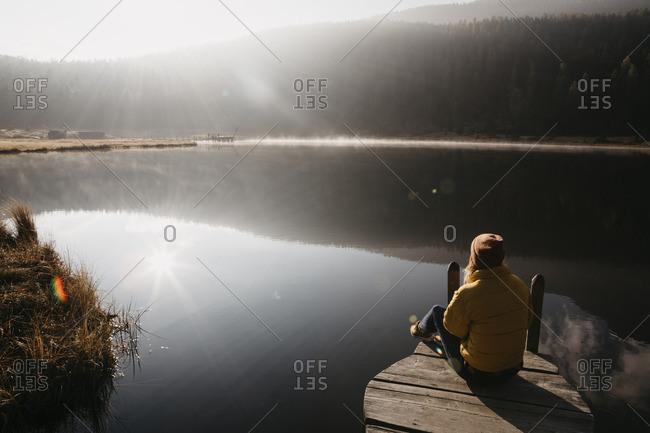 Switzerland- Engadine- Lake Staz- woman sitting on a jetty at lakeside in morning sun